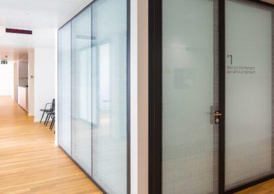 couloirdu CMCF avec vue sur une salle de traitements aux portes en verre fumé